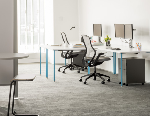 Knoll Antenna Simple tables with blue legs for primary workstations
