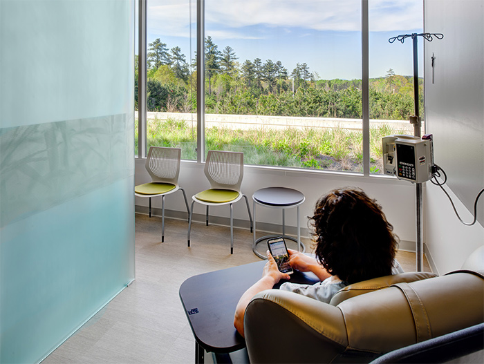 Infusion treatment areas sit at the perimeter of the building, offering patients natural light and views of the surrounding mountains. In addition, movable walls can be closed by patients who wish to have privacy, or opened to connect with others receiving treatment. Featured: MultiGeneration by Knoll<sup>®</sup> Stacking Chairs