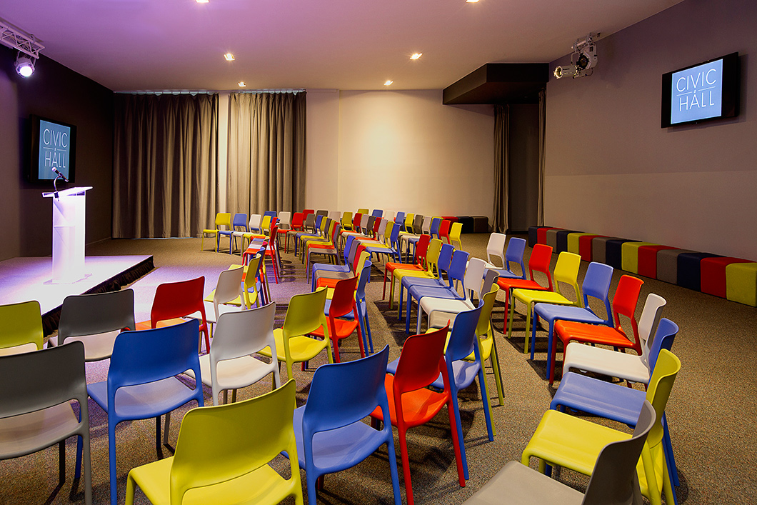 Lightweight stacking chairs and modular ottomans provide maximum flex for a multipurpose space that hosts lectures, receptions, workshops and movies on near-daily regular basis. The bright palette adds a blast of energetic color. | Featured: Spark Series Side Chairs, k. lounge Stools
