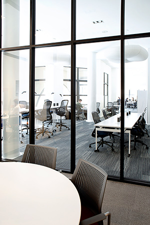 Civic Hall features a mix of open and enclosed workspaces and liberal use of glass to share the daylight that streams in from the huge windows. | Featured: ReGeneration by Knoll Work and High Task Chairs, Antenna Workspaces Tables, Sparrow Desktop Lights, MultiGeneration by Knoll Hybird Chairs